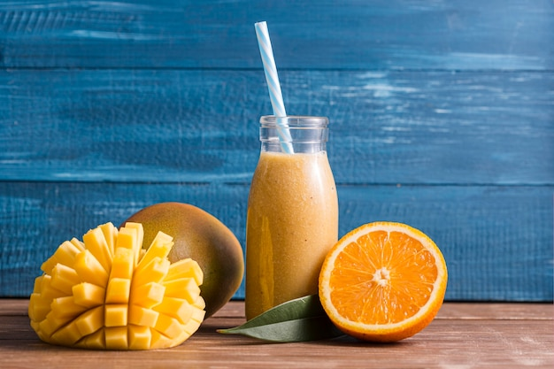 Front view mango and orange smoothie in bottle Premium Photo