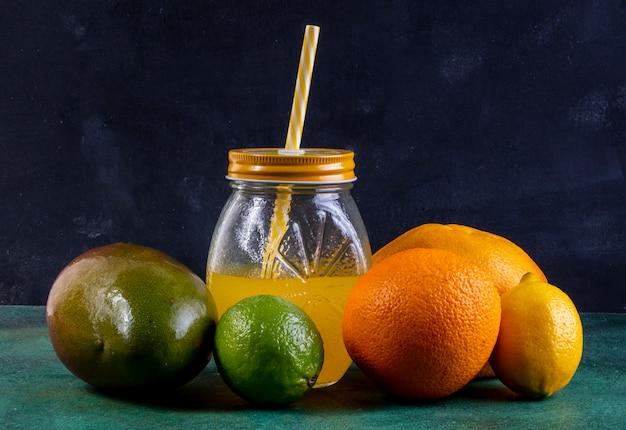 レモンライムオレンジと黄色のストローが付いている瓶にジュースとマンゴーの正面図 無料写真