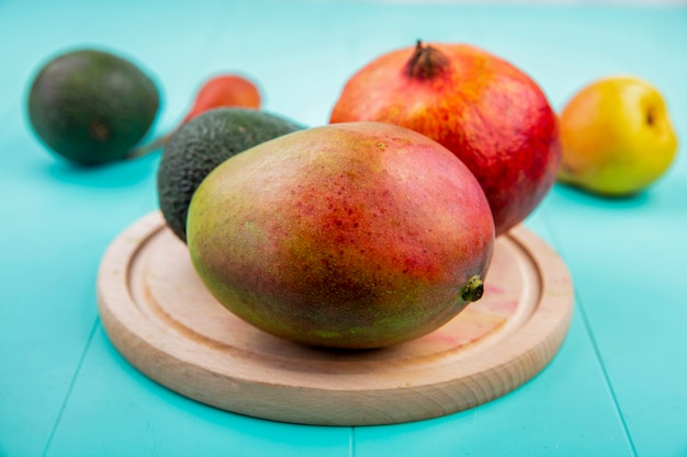 Front view of mango with pomegranate on a wooden kitchen board on blue surface Free Photo