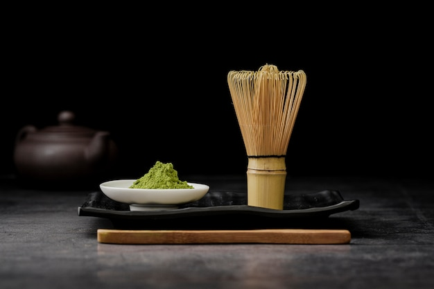 Front view of matcha tea powder with bamboo whisk Free Photo