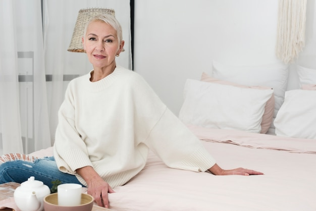 Front view of mature smiley woman posing in bed with copy space Free Photo