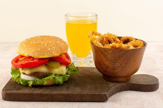 Un hamburger di carne di vista frontale con succo di formaggio e insalata verde e ali di pollo sul tavolo di legno Foto Gratuite