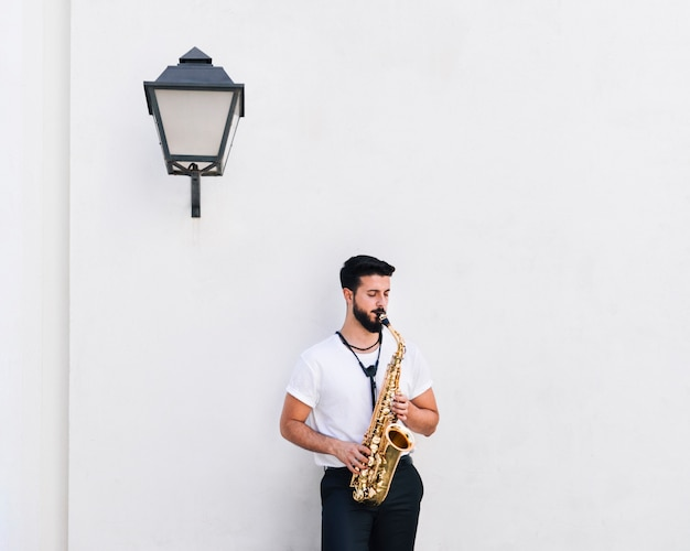 Front view medium shot musician playing the saxophone Free Photo