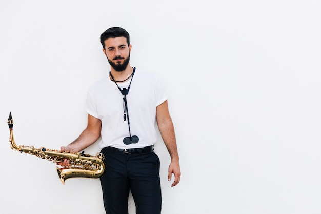 Front view medium shot musician posing with saxophone Free Photo