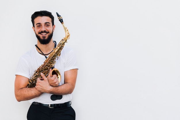Front view medium shot smiling musician with saxophone Free Photo