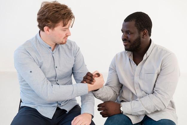 Uomini di vista frontale che si tengono per mano e che si consolano Foto Gratuite