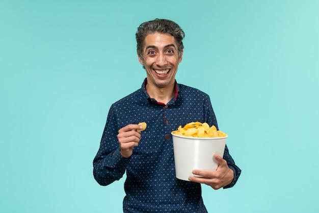 正面図中年男性がcipsを食べて青い表面で笑っている 無料写真
