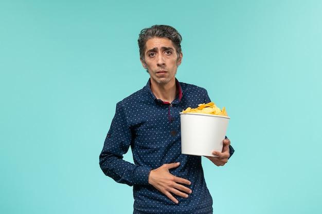 青い表面にcipsを食べる中年男性の正面図 無料写真