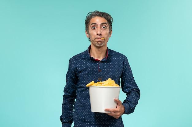 正面図中年男性は、cipsと水色の表面で食べるバスケットを保持しています 無料写真