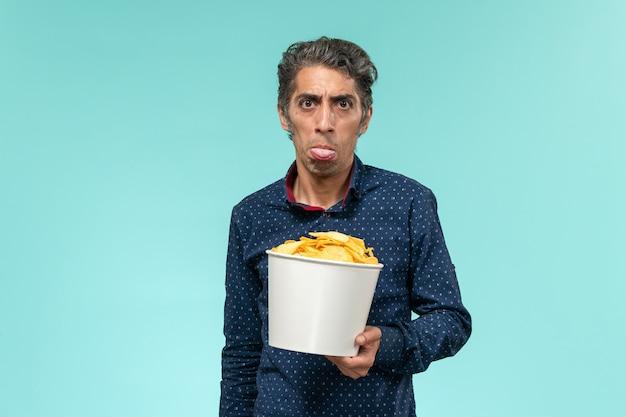 正面図中年男性はcipsを保持し、青い表面で食べる 無料写真
