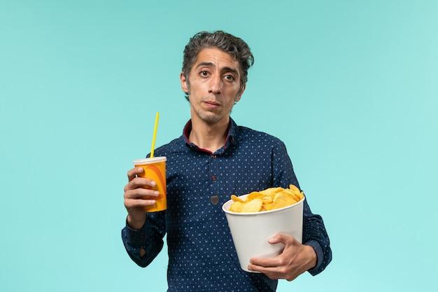ジャガイモのcipsを保持し、青い表面で飲む中年男性の正面図 無料写真