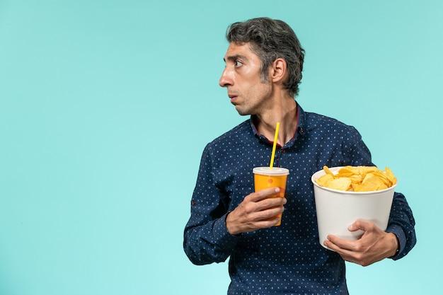 青い表面にジャガイモのcipsとソーダを保持している正面図中年男性 無料写真