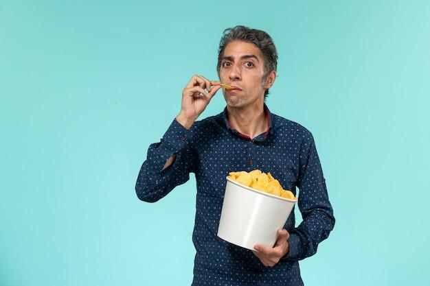 Cipsでいっぱいのバスケットと青い表面で食べる中年男性の正面図 無料写真