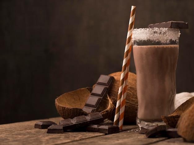 Vista frontale del frullato di vetro sul vassoio con cocco e cioccolato Foto Gratuite