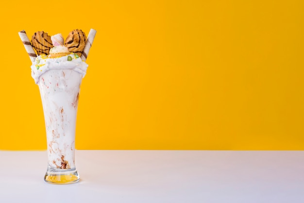 Front view of milkshake with yellow background and copy space Free Photo