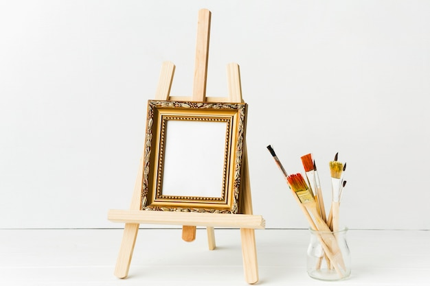 Front view minimalist frame on easel and brushes Free Photo