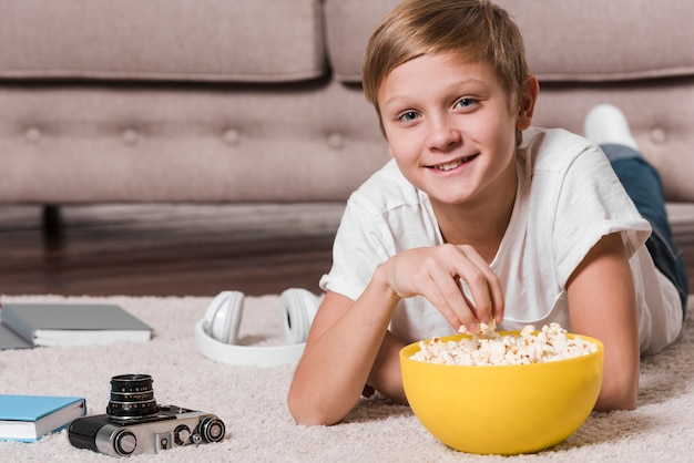 Front view of modern boy eating popcorn Free Photo