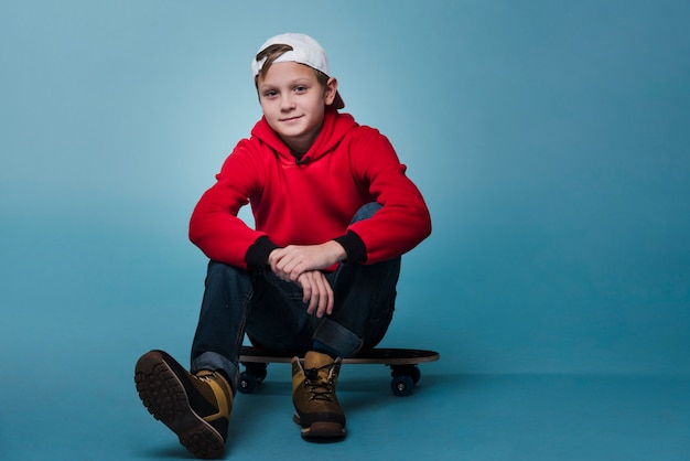 Front view of modern boy sitting on skateboard Free Photo
