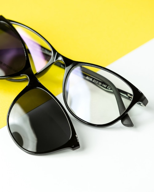 A front view modern dark sunglasses pair on the white-yellow Free Photo
