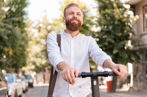 Uomo moderno di vista frontale sul motorino Foto Gratuite
