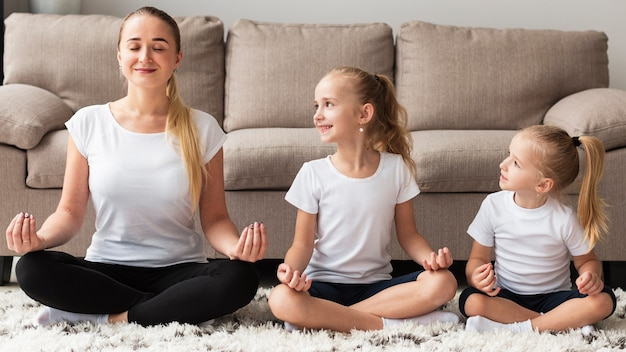 Front view of mother doing yoga with daughters at home Free Photo