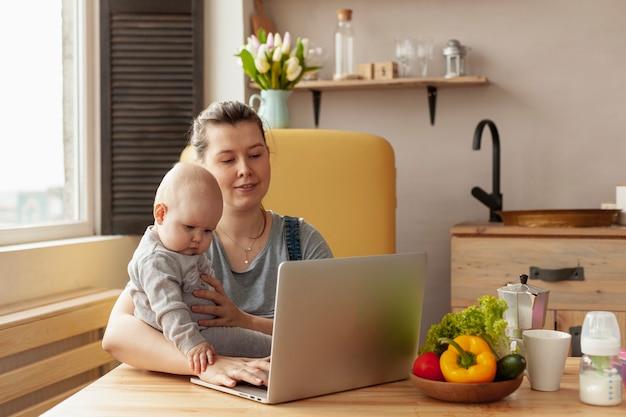 Madre di vista frontale con il bambino a casa Foto Gratuite