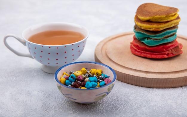 正面図色のチョコレートと白い背景の上のお茶とスタンドの色とりどりのパンケーキ 無料写真