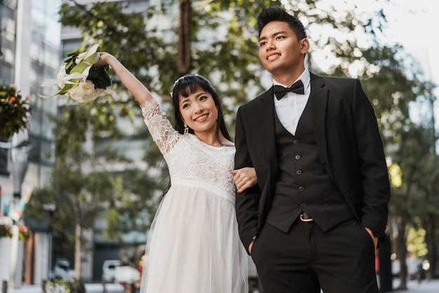 Vista frontale degli sposi sorridenti all'aperto Foto Gratuite
