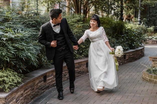 Vista frontale degli sposi che camminano per strada Foto Gratuite