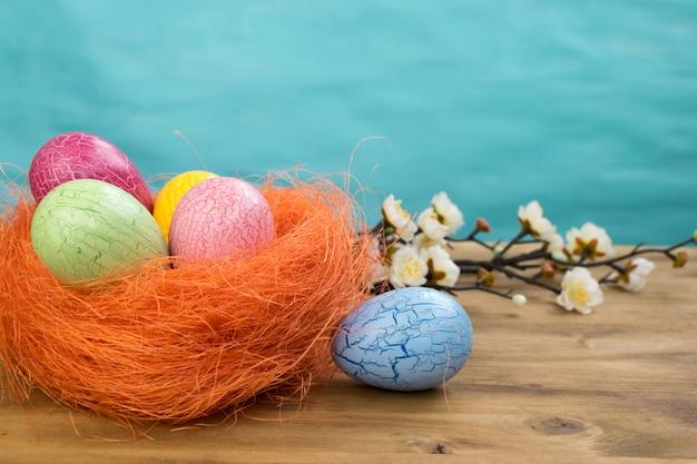 Вид спереди пасхальных яя в оранжевом гнезде и цветках весны на предпосылке древесины и бирюзы с космосом сообщения. Premium Фотографии
