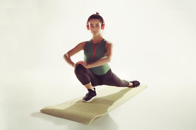 体操のクラスで体を伸ばす若い女性の正面図。 無料写真