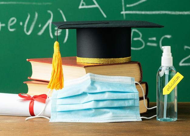 Вид спереди академической кепки на книгах с медицинской маской и дезинфицирующим средством для рук Бесплатные Фотографии