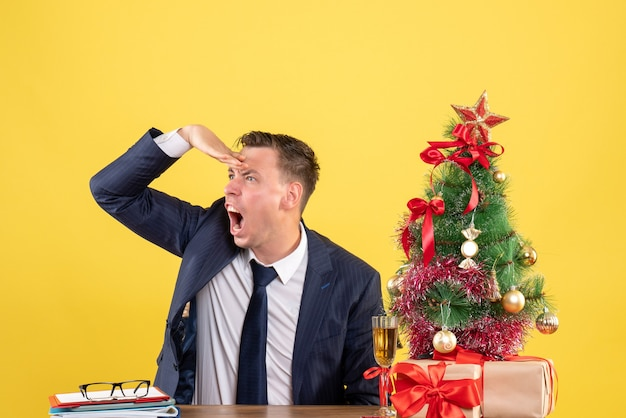 クリスマスツリーの近くのテーブルに座って黄色の壁にプレゼントを観察している怒っている男の正面図 無料写真
