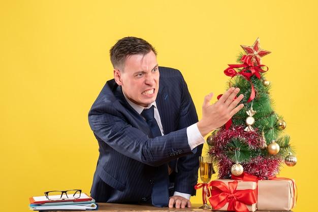 Вид спереди разгневанного человека, стоящего за столом возле елки и подарков на желтой стене Бесплатные Фотографии