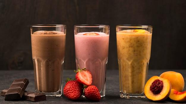Вид спереди ассортимента молочных коктейлей с фруктами и шоколадом Premium Фотографии