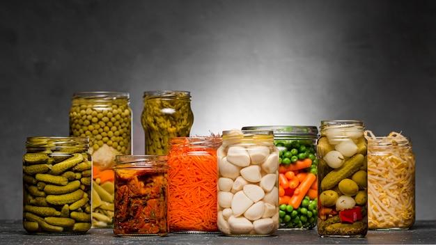 ガラスの瓶に漬け込んだ野菜の品揃えの正面図 Premium写真