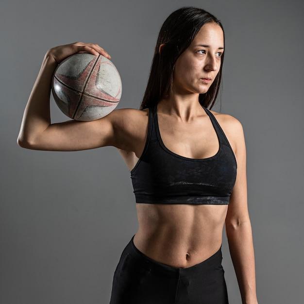 Вид спереди спортивного женского регбиста, держащего мяч Бесплатные Фотографии