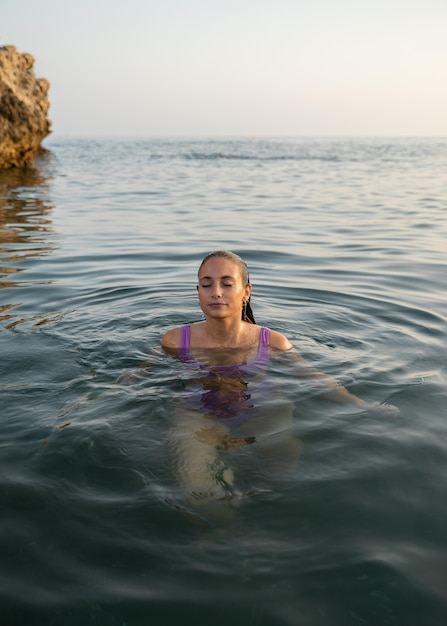 Вид спереди красивой женщины на пляже Premium Фотографии