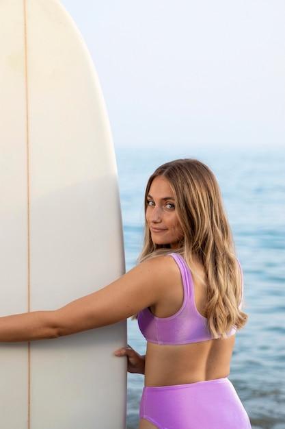 Вид спереди красивой женщины с доской для серфинга Бесплатные Фотографии