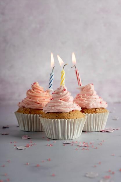 アイシングと点灯ろうそくと誕生日カップケーキの正面図 Premium写真