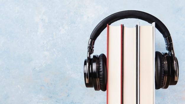 Вид спереди книг и наушников с копией пространства Premium Фотографии