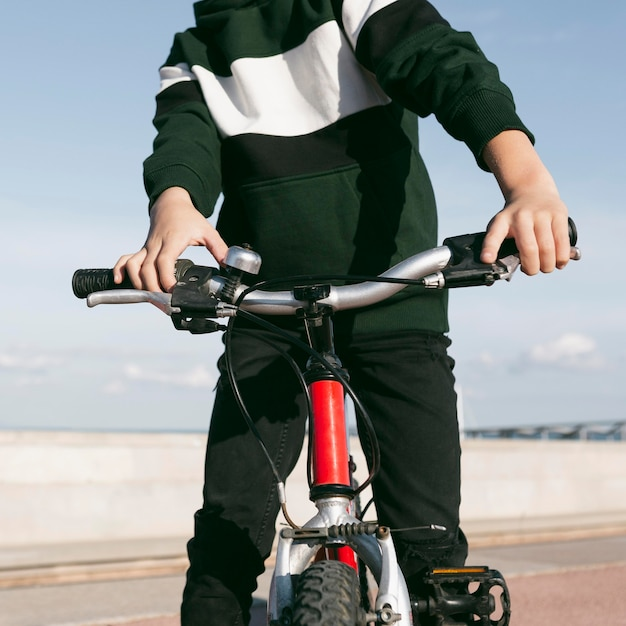 밖에 서 그의 자전거와 소년의 전면보기 무료 사진