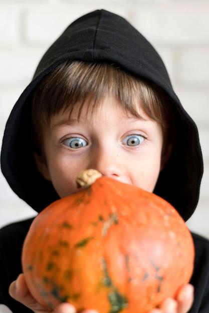 Вид спереди мальчика с концепцией костюма тыквы Premium Фотографии
