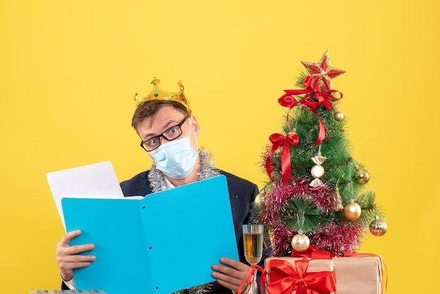 クリスマスツリーの近くのテーブルに座って、黄色の壁に提示するドキュメントをチェックするビジネスマンの正面図 無料写真