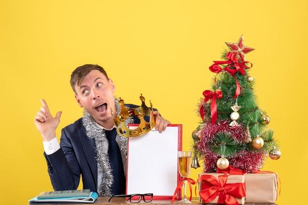 クリスマスツリーの近くのテーブルに座ってクリップボードと王冠を保持し、黄色で提示するビジネスマンの正面図 無料写真