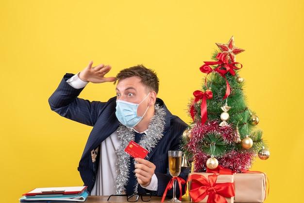 クリスマスツリーの近くのテーブルに座って黄色で提示する何かを観察しているビジネスマンの正面図 無料写真