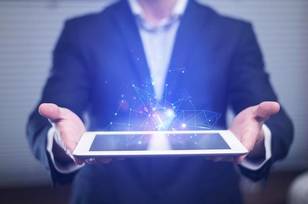ハイテクタブレットを保持している実業家の正面図 Premium写真