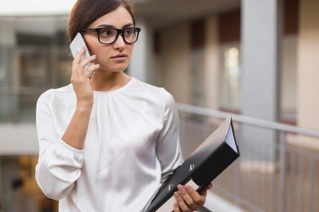 Вид спереди бизнес-леди разговаривает по телефону, держа в руках связующее Бесплатные Фотографии