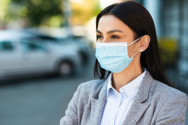 医療マスクとコピースペースを持つ実業家の正面図 Premium写真
