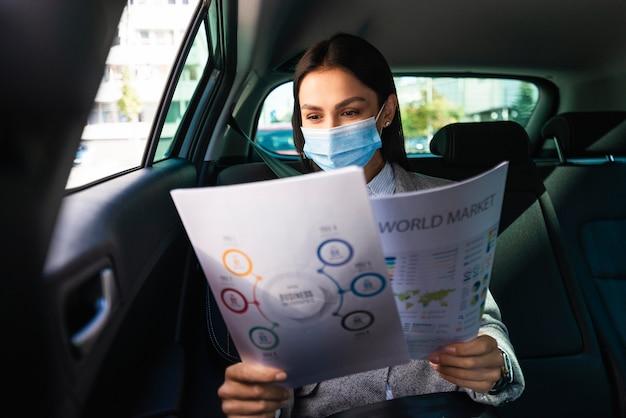文書を確認する車の中で医療マスクを持つ実業家の正面図 Premium写真